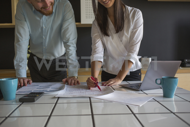 Smiling man and woman studying plans on table at home - MOMF00371 - Mosuno Media/Westend61