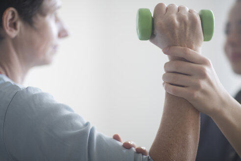 Physiotherapist and patient, training with dumbbell - SGF02132