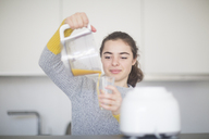 Portrait of smiling woman pouring freshly squeezed orange juice into a glass in the kitchen - SGF02135