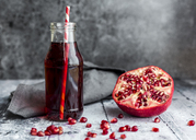 Sliced pomegranate and glass bottle of pomegranate juice - SARF03456