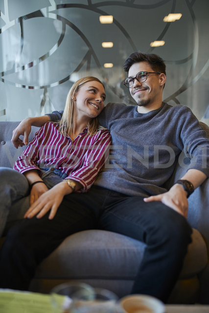 Happy relaxed couple sitting on sofa in a cafe - ZEDF01052