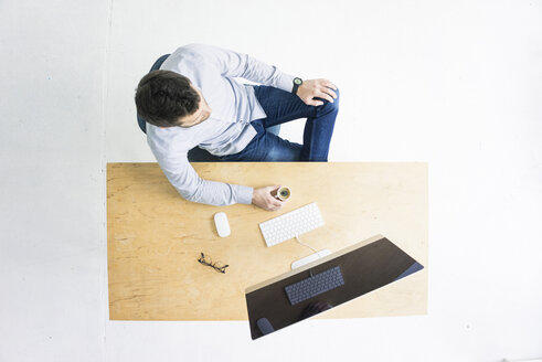 Businessman sitting at desk in office seen from above - MOEF00635