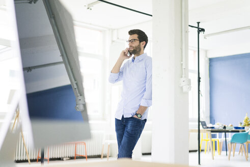 Businessman on cell phone in office - MOEF00638