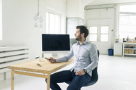 Businessman with cell phone sitting at desk in office - MOEF00641