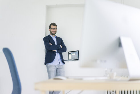 Portrait of smiling businessman standing in office - MOEF00659