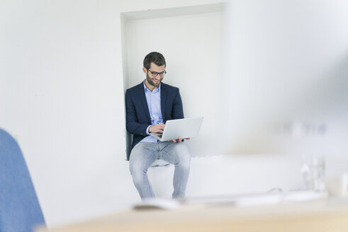 Smiling businessman sitting in a niche using laptop - MOEF00662