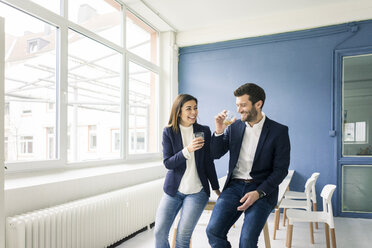 Happy businessman and businesswoman with drinks in office - MOEF00668