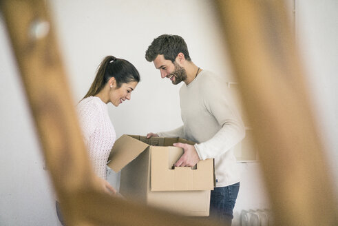 Couple moving into new home unpacking cardboard boxes - MOEF00680