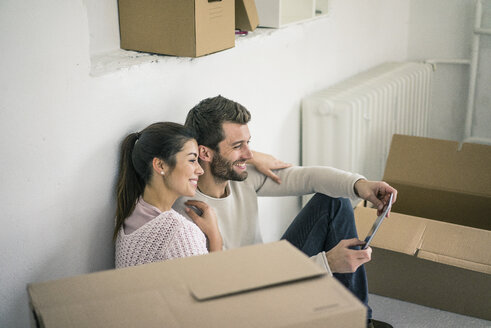 Couple sitting in new home surrounded by cardboard boxes looking at tablet - MOEF00683