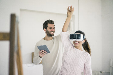 Man lifting woman's arm wearing VR glasses in new home - MOEF00689