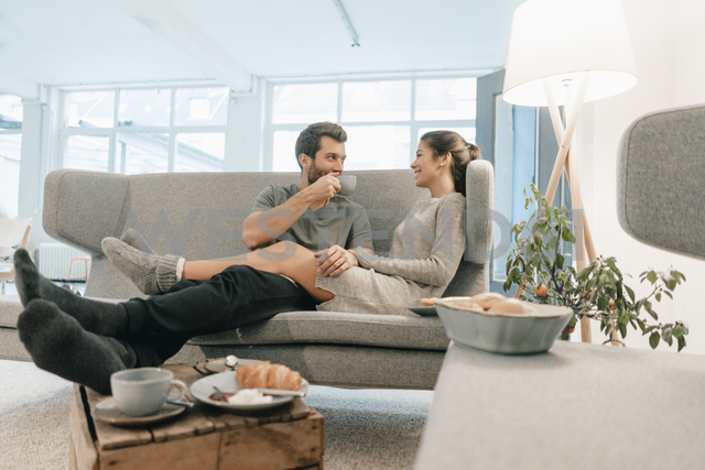 Couple relaxing on couch at home having breakfast - MOEF00692 - Robijn Page/Westend61