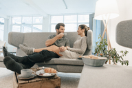 Couple relaxing on couch at home having breakfast - MOEF00692