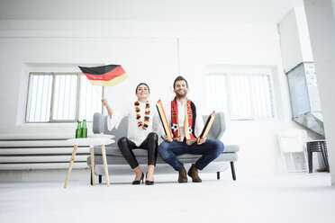 Happy German football fan couple sitting on couch watching Tv - MOEF00695