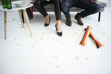 Legs of German football fans sitting on couch with chips scattered on the floor - MOEF00698