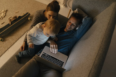 Family using laptop on the couch in the dark - KNSF03394
