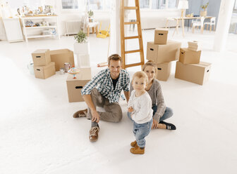 Portrait of smiling family moving into new home - KNSF03397