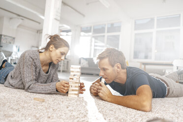 Couple lying on the floor playing jenga - KNSF03406
