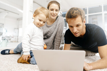 Family using laptop on the floor - KNSF03409