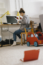 Woman sitting at desk at home surrounded by toys - KNSF03418