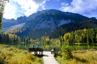 Germany, Bavaria, Upper Bavaria, Chiemgau, Inzell, Frillensee, hikers sitting on bench in autumn - LBF01728