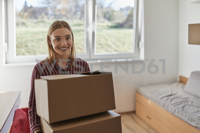 Portrait of smiling young woman carrying cardboard boxes - ZEDF01075