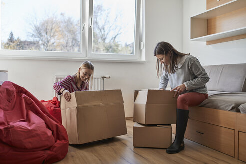 Two young women unpacking cardboard boxes in a room - ZEDF01078