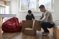 Two young men unpacking cardboard boxes in a room - ZEDF01081