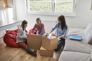 Three young women unpacking cardboard boxes in a room - ZEDF01084