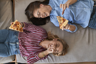 Two laughing young women lying down eating pizza together - ZEDF01096