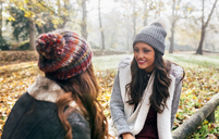 Two pretty women relaxing in an autumnal forest - MGOF03695
