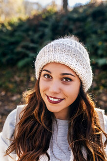 Portrait of a beautiful smiling woman wearing wooly hat - MGOF03704