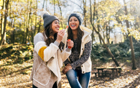 Two beautiful women having fun with soap bubbles in an autumnal forest - MGOF03707