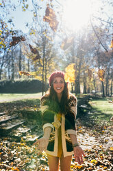 Portrait of a beautiful happy woman having fun with leaves in an autumnal forest - MGOF03710