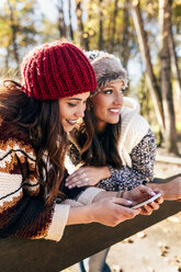 Two pretty women using smartphone in an autumnal forest - MGOF03713