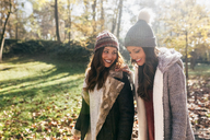 Two pretty women walking in an autumnal forest - MGOF03725