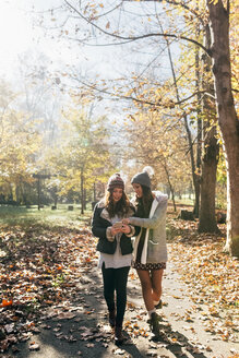 Two women with cell phone walking in autumnal forest - MGOF03728