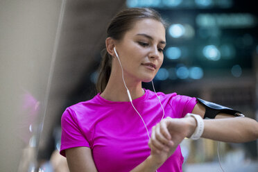 Young woman in pink sportshirt listening to music and checking her smartwatch - SBOF00979