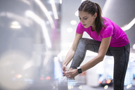 Young woman in pink sportshirt listening to music and tying her sneakers - SBOF00982