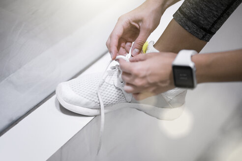 Close up of female hands tying sneakers with smartwatch - SBOF00988