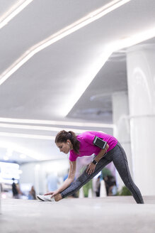 Young woman in pink sportshirt listening to music and stretching in front of modern building - SBOF00991