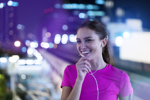 Smiling young woman in pink sportshirt listening to music in city at night - SBOF00994