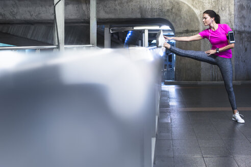 Young woman in pink sportshirt stretching in modern metro station - SBOF01000