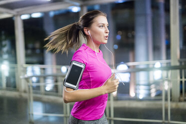 Young woman in pink sportshirt running in city at night - SBOF01003