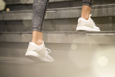 Close up of female legs with white sport sneakers running up the stairs - SBOF01006