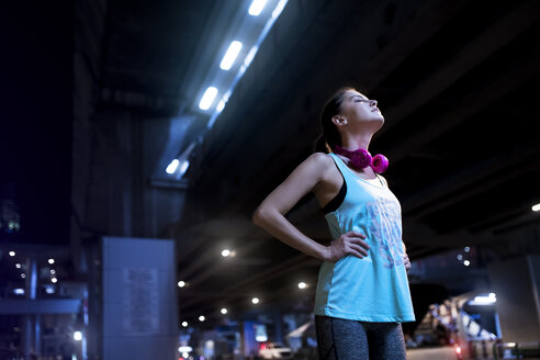Young woman with pink headphones in modern urban setting at night - SBOF01009
