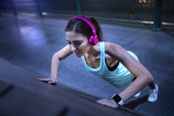Young woman with pink headphones doing pushups in modern urban setting at night - SBOF01012