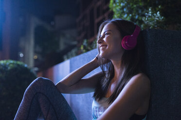 Happy young woman with pink headphones listening to music in modern urban setting at night - SBOF01021