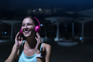 Happy young woman with pink headphones listening to music in modern urban setting at night - SBOF01024