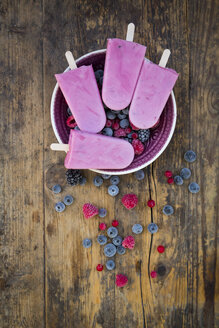 Homemade wild-berry ice lollies with raspberries, blueberries, red currants and blackberries in a bowl - LVF06599