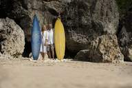 Affectionate senior couple with surfboards at beach - SBOF01032